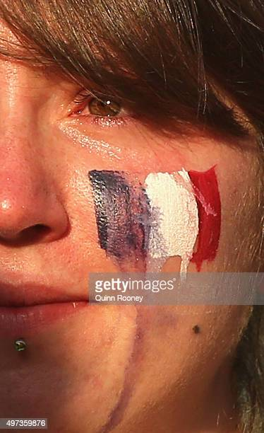 Tears run down the face of a lady as people gather for a vigil to honour victims of the Paris terror attacks at Federation Square on November 16 2015...