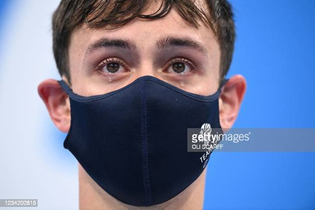 Tears well in the eyes of gold medallists Britain's Thomas Daley and Britain's Matty Lee as they wait to receive their medals after wining the men's...