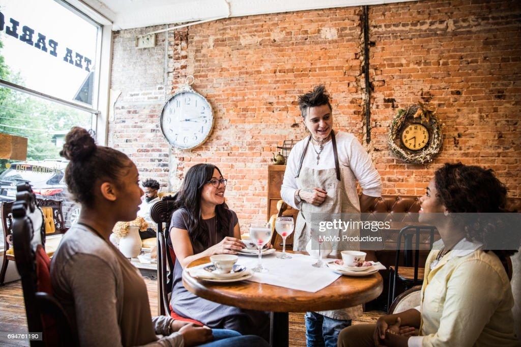 Teashop owner serving tea to group : Stock Photo