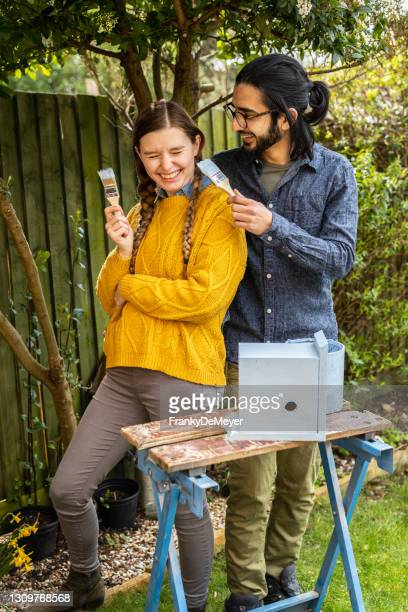 teasing each other with paintbrush. young multi-ethnic couple running a home woodworking business together, painting a birdhouse in the garden - mid adult stock pictures, royalty-free photos & images