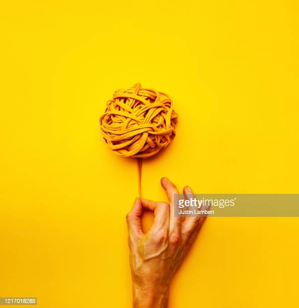 teasing out a thread from a ball of yellow yarn on a bright yellow backdrop - absence stock pictures, royalty-free photos & images