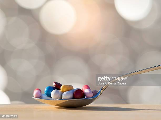 teaspoon of medicines in tablets and pills.  medicine abuse - euthanasia stock pictures, royalty-free photos & images