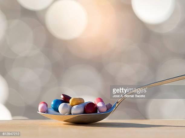 teaspoon of medicines in tablets and pills.  medicine abuse - eutanasia fotografías e imágenes de stock