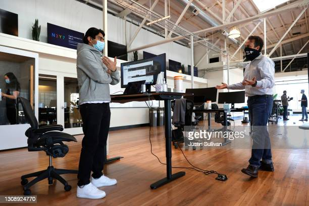 Tech startup company Fast Chief Communications Officer Jason Alderman talks with an employee on the first day working in the office on March 24, 2021...