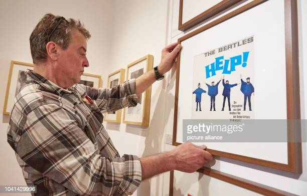 Technical assistant Klaus Volcsik hangs up the record sleeve for Help by The Beatles for the exhibition John Lennon Imagine Musiker Poet Zeichner...