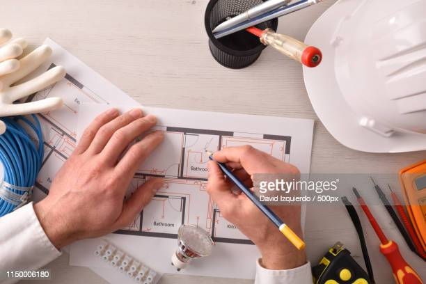 technical engineer in electricity writing in an electrical plan - 人工物 ストックフォトと画像