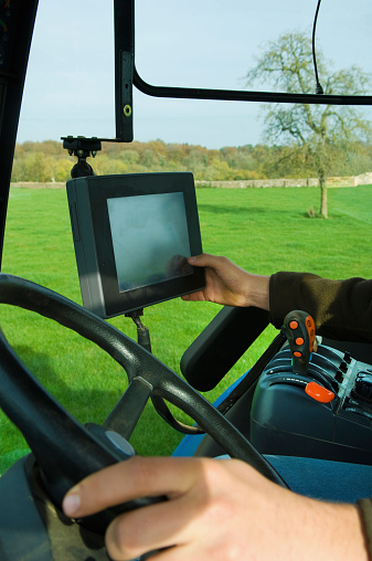 Technical equipment aboard a tractor, a hand touching a computer touch screen. - gettyimageskorea