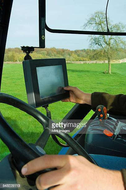 Technical equipment aboard a tractor, a hand touching a computer touch screen.