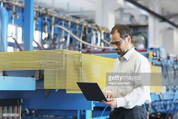 Technical manager checking information on laptop