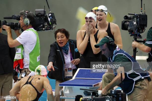 A technical official trys to stop Melanie Schlange of Australia climbing out of the pool to celebrate victory with teammates Alicia Coutts and Cate...