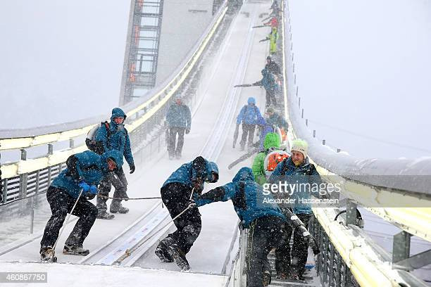 Technicans prepare the jumping hill during a break in the heavy snow and windy conditions on day 2 of the Four Hills Tournament Ski Jumping event at...