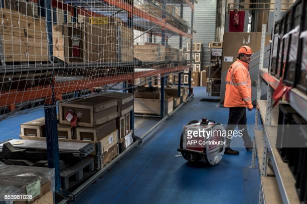 technicentre technician works alongside an industrial droid assistant on September 25 2017 in Oullins near Lyon Developed by the Lyonbased startup...