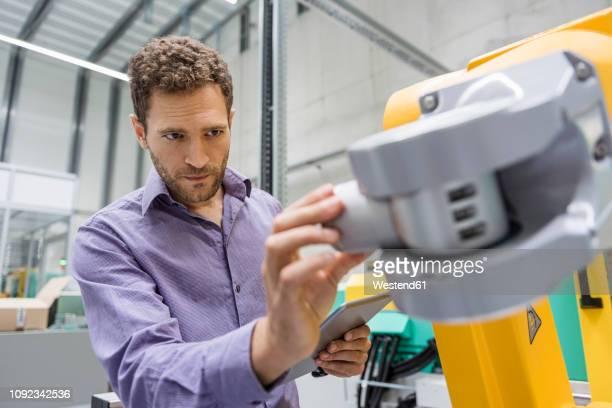 technician adjusting industrial robot - concentrazione foto e immagini stock