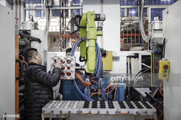 A technician adjusts an industrial robot manufactured by the EDeodar Robot Equipment Co a whollyowned subsidiary of Ningbo Techmation Co as it stands...
