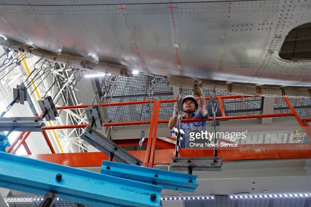 A technician adjusts China's first domestically made C919 passenger jet before its trial flight on June 25 2018 in Shanghai China The C919 aircraft...