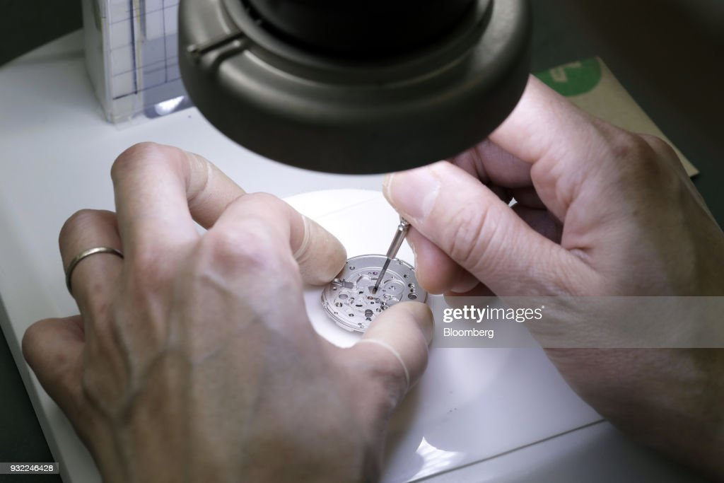 A technician assembles mechanical movement parts of a Grand