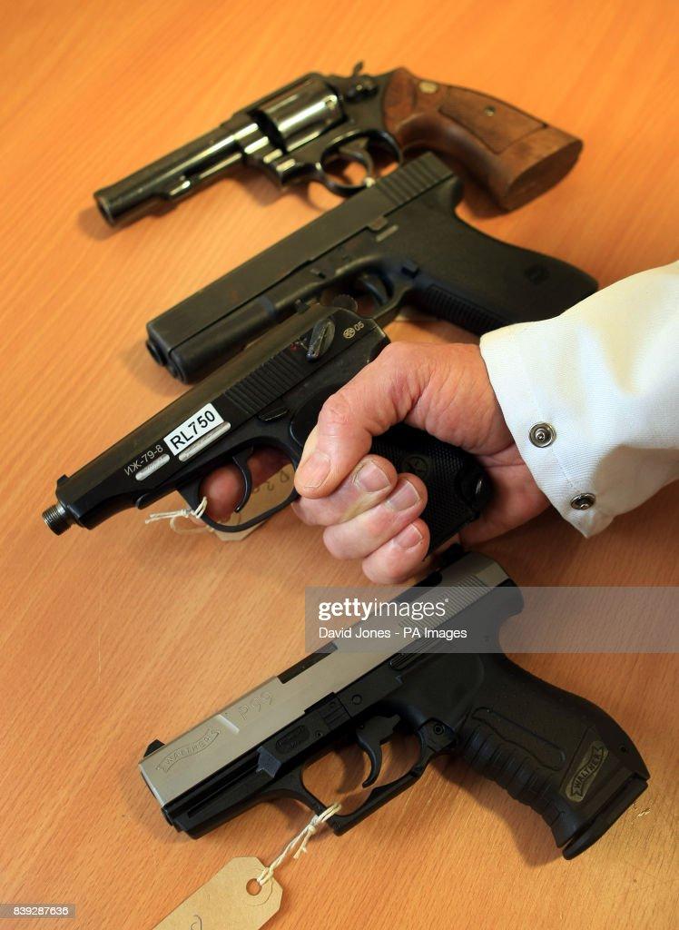 A technician at a NABIS laboratory holds a 'Baikal' handgun