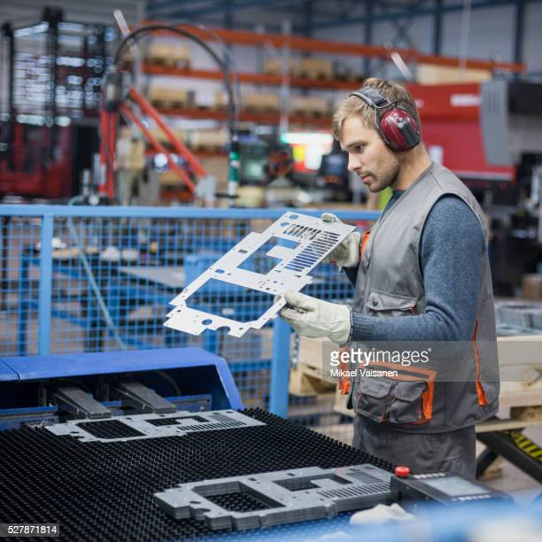 technician at work in sheet metal component factory