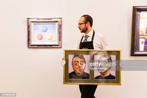 A technician carries Francis Bacon's Two Studies for a SelfPortrait in front of Rene Magritte's Les Jeunes amours 1963 at Sotheby's on April 8 2016...