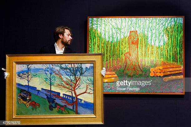A technician carrys Andre Derains's view of London 's Embankment in front David Hockney's Arranged Felled Trees in prepartion for the Masterworks In...