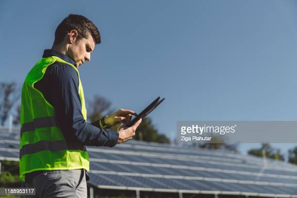 technician cheching the power supply on digital tablet - solar mirror stock pictures, royalty-free photos & images