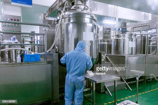 Technician check manufacture equipment and reactors in pharmacy factory