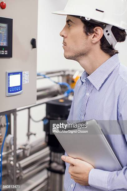 Technician checking industrial equipment in operation at plant