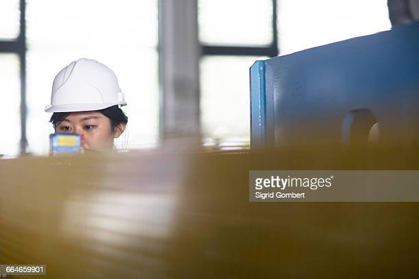 technician checking readings on gauge in factory - sigrid gombert stock-fotos und bilder