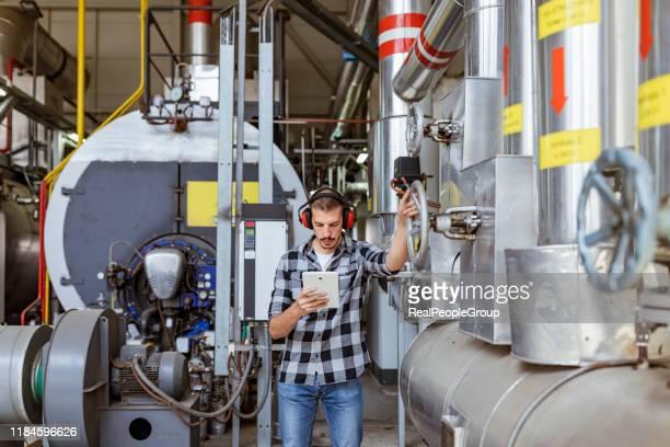 technicus die het systeem controleert - industriële apparatuur stockfoto's en -beelden