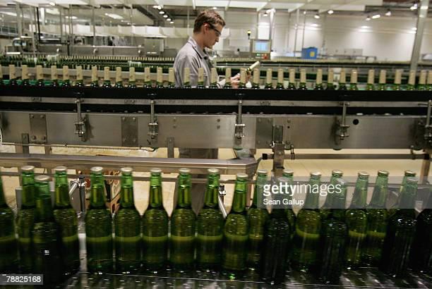 A technician checks a bottle as other bottles of freshlybrewed PilsnerUrquell lager beer run through the newlybuilt ultramodern bottling plant at the...
