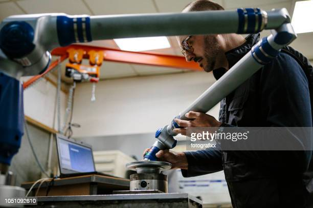 Technician checks a metal part with a robotic arm in a metal manufacturing company