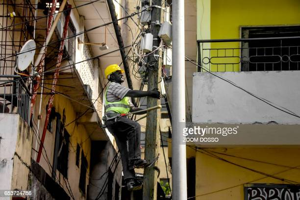 A technician checks an electric pole in downtown Monrovia on February 21 2017 Liberia is making a giant leap into an electrified future with the...
