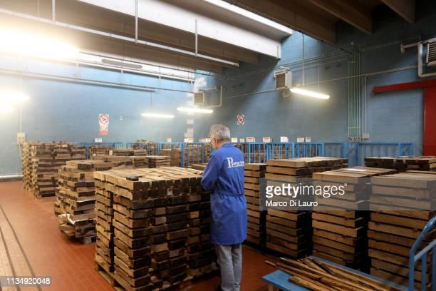 A technician checks stacks of piece of wood for gunshot stock on April 4 2019 at the Perazzi Armi factory in Botticino Mattina a village in the...