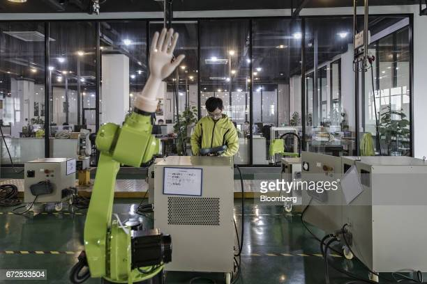 A technician controls an industrial robot fitted with an artificial hand on the testing line of a factory operated by EDeodar Robot Equipment Co a...