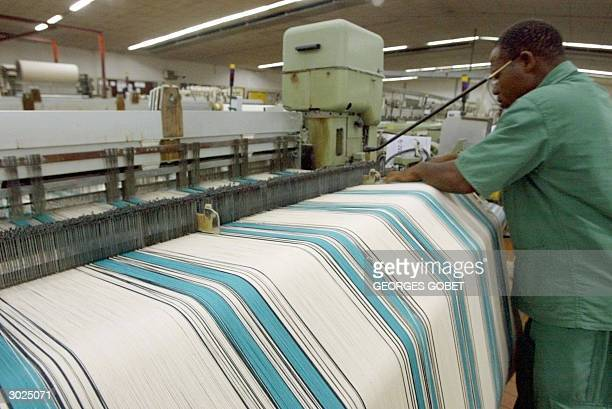Technician controls the quality of cotton cloth at the Filature Tissage Gonfreville textile factory 26 February 2004 in the northern Ivorian city of...