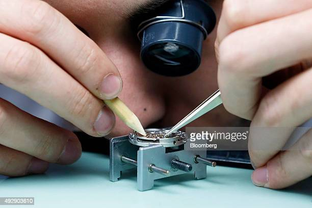 A technician disassembles the workings of a luxury wristwatch in the aftersales department at the Patek Philippe SA headquarters and manufacturing...
