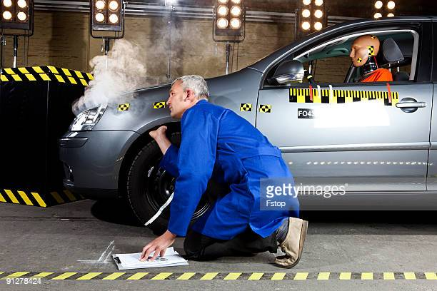 A technician examining a smoking crash test car wi