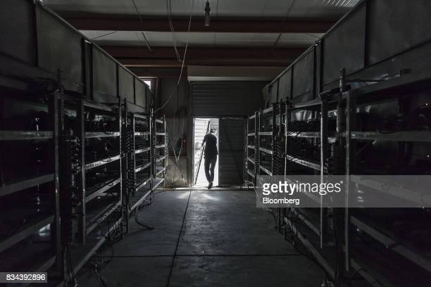 A technician exits a warehouse containing bitcoin mining machines at a mining facility operated by Bitmain Technologies Ltd in Ordos Inner Mongolia...
