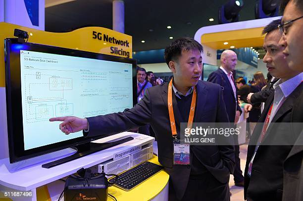 A technician explains to visitors the Network 5G operation at the SK Telecom's stand at the Mobile World Congress in Barcelona on February 22 on the...