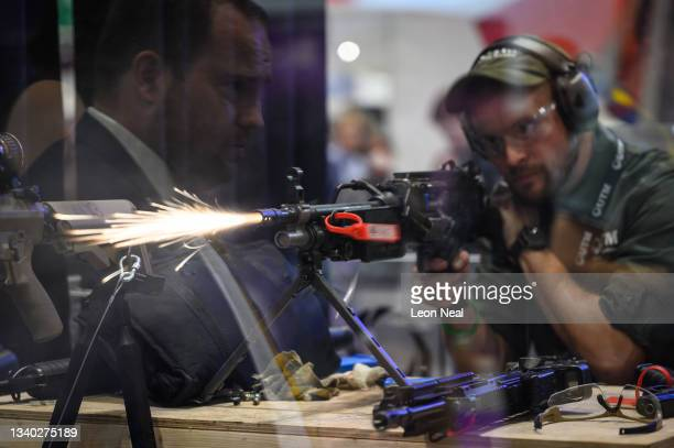 Technician fires blank rounds from a light machine gun on the Ultimate Training Munitions testing area on day one of the DSEI exhibition at ExCel on...