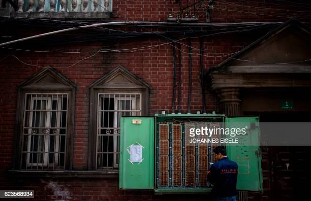A technician fixes connections for a landline telephone switch box at a residential compound in Shanghai on November 16 2016 Some 216 million people...