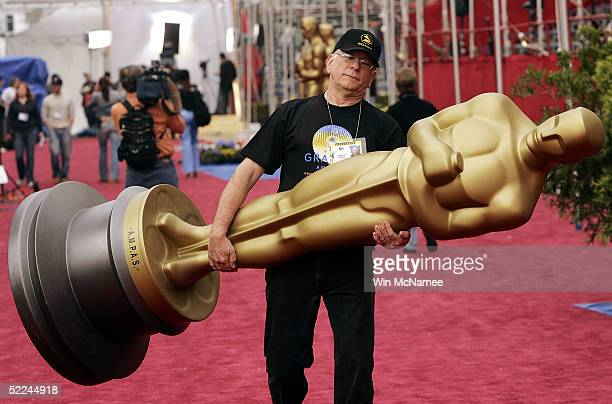 Technician Fred Kelpik carries an Oscar statue during preparation for the 77th Academy Awards at the Kodak Theater February 26, 2005 in Hollywood,...