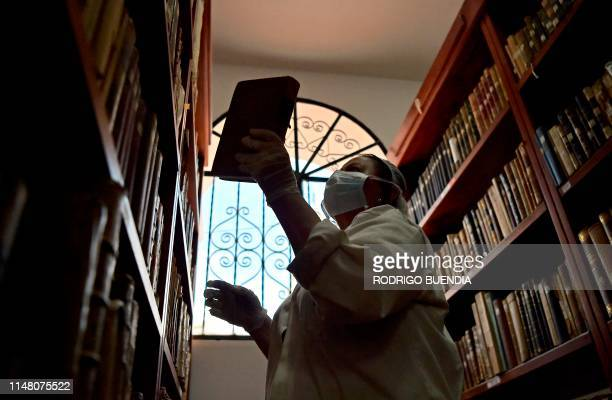 A technician from Conservartecuador works on the preservation and organization of the Fray Ignacio de Quezada library at the Convent of Santo Domingo...