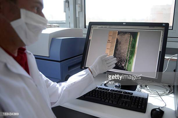 A technician from the French national forensic institute shows on a screen a picture of a fingerprint at the laboratory of the central police station...