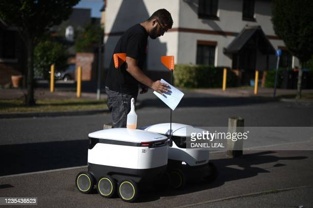 Technician from the grocery delivering company Starship cleans an autonomous robot before a delivery run outside a local Co-op supermarket in Milton...