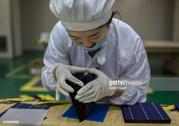 A technician from Yingli Solar checks a cell used in solar panels on a production line at the company's headquarters on December 4 2014 in Baoding...