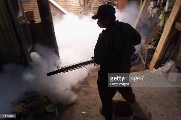 Technician fumigates a home in a poor neighbourhood July 25, 2002 in Tegucigalpa, Honduras. Haemorrhagic Dengue, a possibly fatal disease spread by...