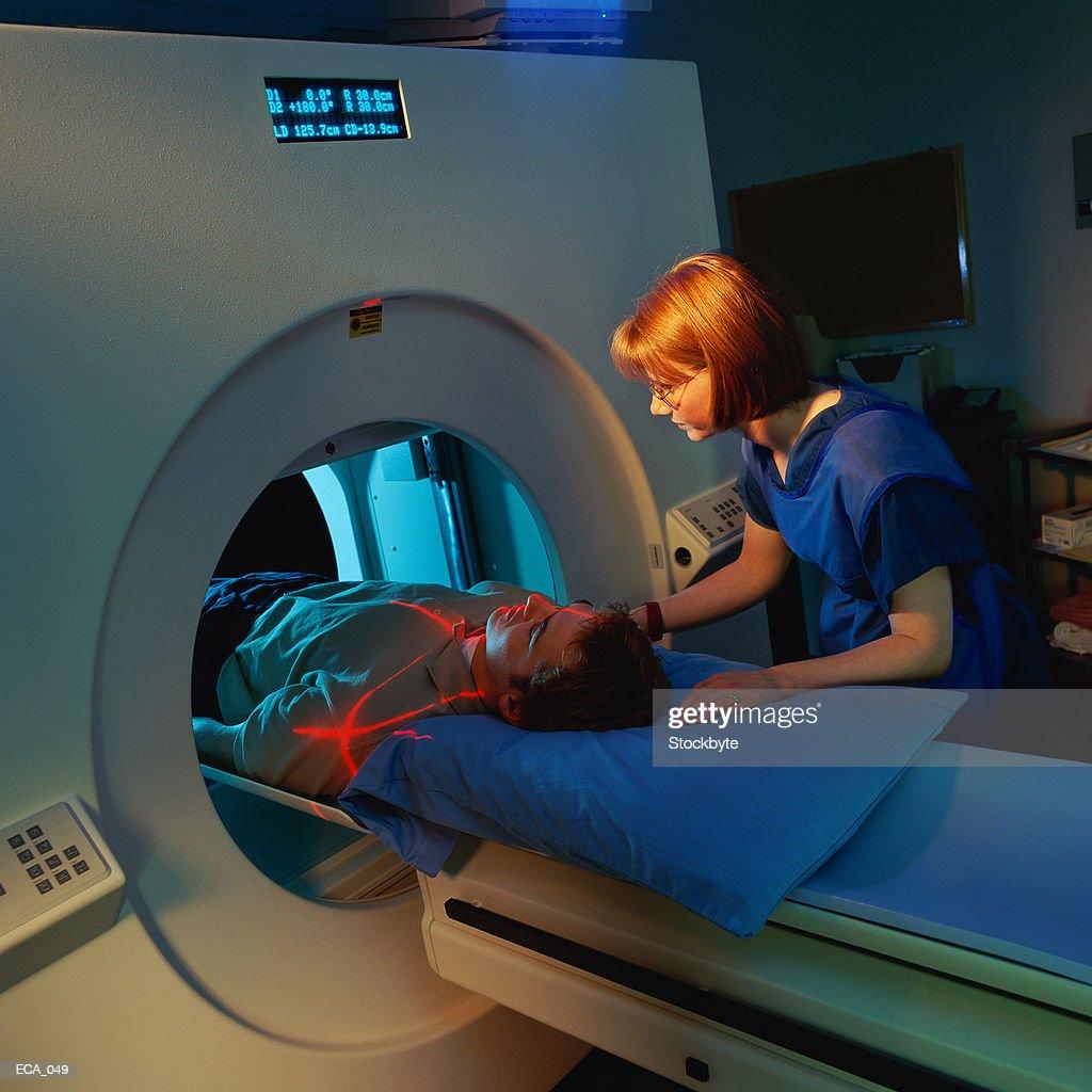 Technician giving man CAT scan : Stock Photo