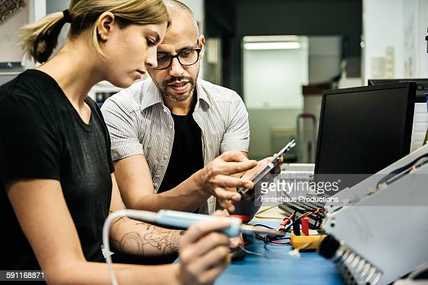 Technician guiding female trainee in workshop