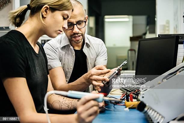 Technician guiding female trainee in workshop